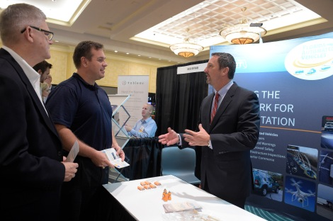 David Sherman, right, talks with Mark Wilson, left, and Russell Allen of the FDOT, during the 2nd Annual Data Symposium in Championsgate, Fla., Tuesday, Aug. 18, 2015. More than 400 attendees from across the nation gathered at the symposium, sponsored by the Florida Department of Transportation to share ways to use big data to improve transportation safety and efficiency. (AP Photo/Phelan M. Ebenhack)